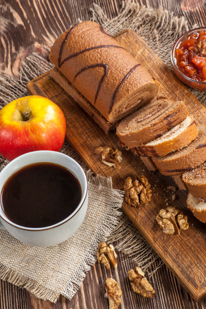 yule log: Tasty cake roll and cofee on old wooden table. Rustic style Stock Photo
