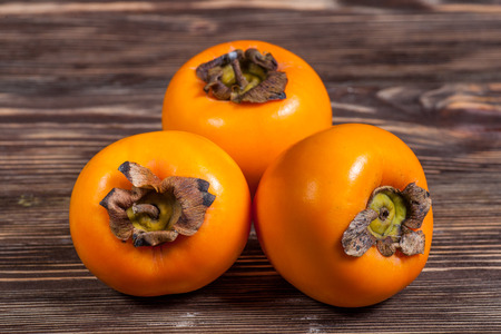 Persimmon fruit on rustic old wooden table