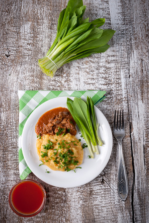 albondigas: peas cooked with meat sauce and ramsons on a wooden table