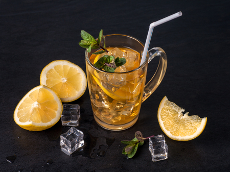 A glasses of iced tea with lemon on black graphite table
