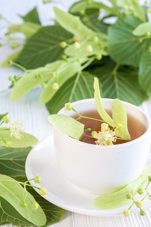 Lime  flower  tea in white porcelain cup with linden flower on wooden table