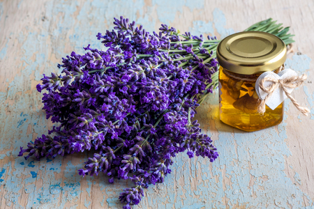 Lavander with aromatic oil on old wooden background