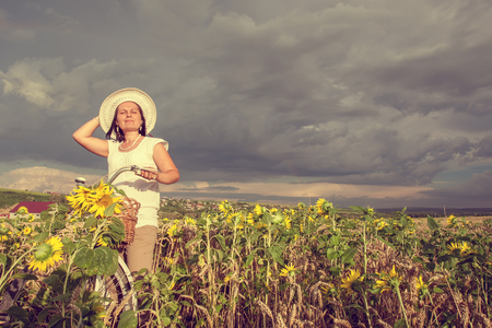 Woman in field with sunflower photo