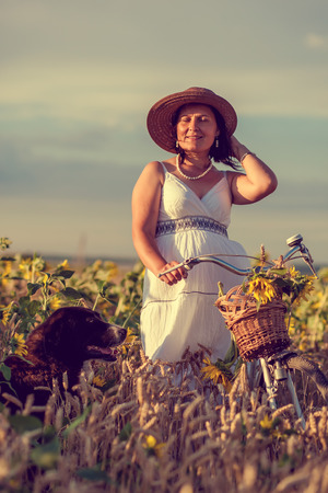 Woman with bicycle and dog in field with sunflower photo