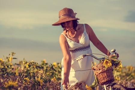 Woman with bicycle in sunflowers field photo