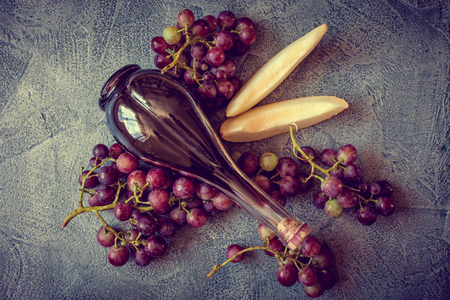 expensive: Grapes with buttle of wine on wintage background Stock Photo