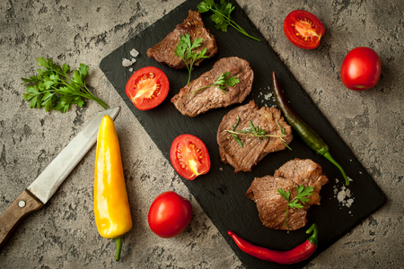 Juicy steak beef with spiced and vegetables on stone table