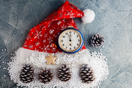 Santas cap with clock and snow on blue vintage background. Happy new year background. Stock Photo