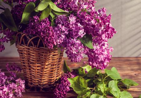 Stillleben mit lila Blumen in rustikaler Vase auf Holztisch Standard-Bild - 98929538