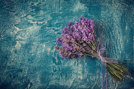 Bouquet of lavender on blue stone background. vspace for text.