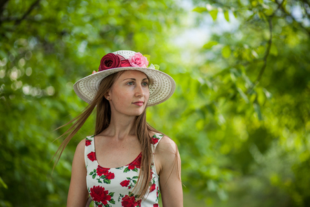 Portrait of a beautiful elegant woman in light white dress and hat standing in the summer park.
