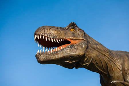 Park of dinosaurs. A dinosaur on the background of nature. Toy dinosaurs in amusement park.
