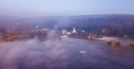 Aerial view The lake and a Thiganeshty Monastery in fog. Autumn landscape. Moldova. Standard-Bild - 113480992