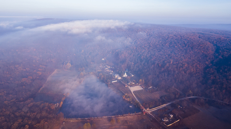 Aerial view The lake and a Thiganeshty Monastery in fog. Autumn landscape. Moldova.