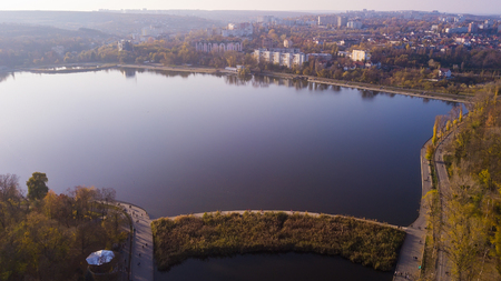 Aerial view of the autumn city park near the lake.