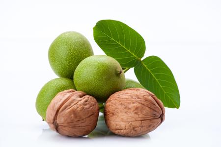 jonge en oude walnoten met bladeren geïsoleerd op een witte achtergrond Stockfoto