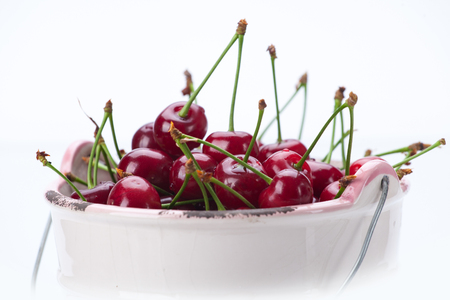 Fresh bird cherry in bowl isolated on white background