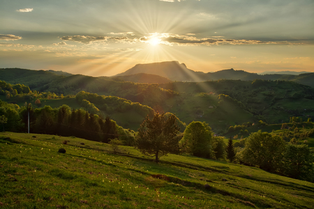 Majestic sunset in the mountains landscape. Carpatian mountains Romania in the spring.