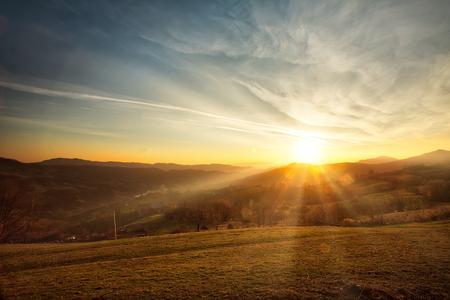 Majestuosa puesta de sol en el paisaje de las montañas. Montañas Carpatian Rumania en la primavera. Foto de archivo