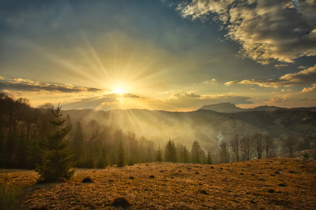 Majestic sunset in the mountains landscape. Carpatian mountains Romania in the spring. Фото со стока