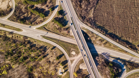 Aerial top down view of interchange road junction traffic. Drone shot flying over crossing roads and railway track. Moldova