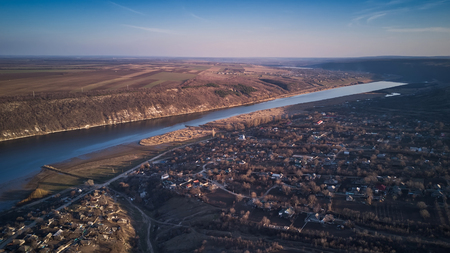 Arial view over the river and small village at sunset. Dniester river of Moldova republic.