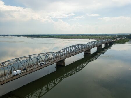 Aerial Drone Flight: View of the bridge over the river with cars. Olt river, Romania