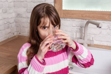 One beautiful Girl drinks water from a glass in the kitchen Zdjęcie Seryjne