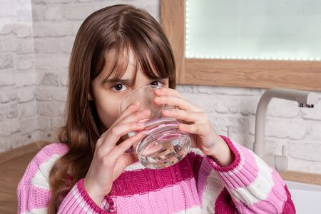 One beautiful Girl drinks water from a glass in the kitchen Zdjęcie Seryjne - 129248597