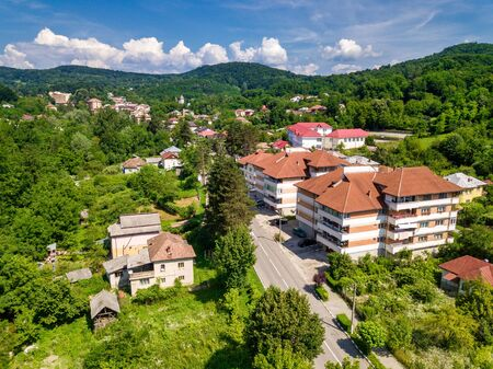 Drone view over the green forest and small city in mountainous area sunny day in summer season.