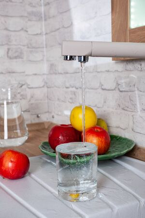 The glass is filled with tap water in the kitchen 스톡 콘텐츠