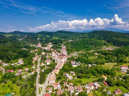 Drone view over the green forest and small city in mountainous area sunny day in summer season. Carpatians mountains, Romania. Imagens