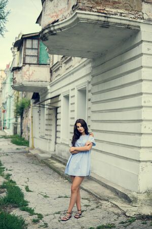 Girl and city. Fashion woman portrait of young pretty trendy brunet girl posing at the city in Europe Stock fotó