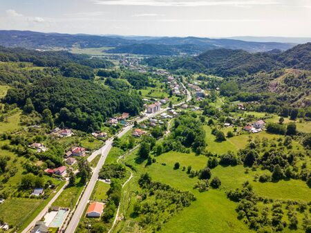 Drone view over the green forest and small city in mountainous area sunny day in summer season. Carpatians mountains, Romania. Stockfoto