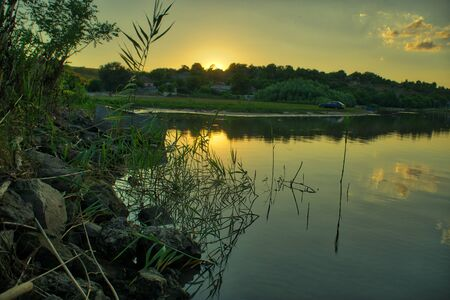 colorful sunset at the river bank in summer
