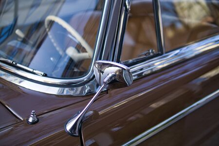 Close up of shiny chrome rear view mirror of classic car. Metal chrome side view mirror attached to the door of vintage car. Old car restoration concept. Reklamní fotografie