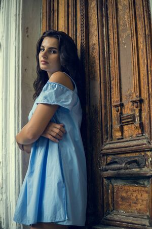 beautiful girl with long hair, in dlue short dress, stands on the background of vintage antique old wooden door