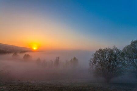 Beautiful foggy autumn sunrise landscape.