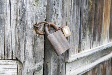 Padlock on an old wooden door Imagens