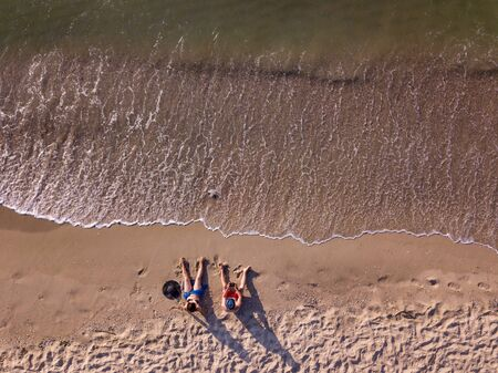 Drone photo. The couple lies on the beach. Top view