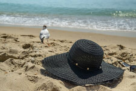 Summer holidays relax on the beach abstract background. Women's hat on the beach sand, against the background of the sea and gulls. Banque d'images - 138293388