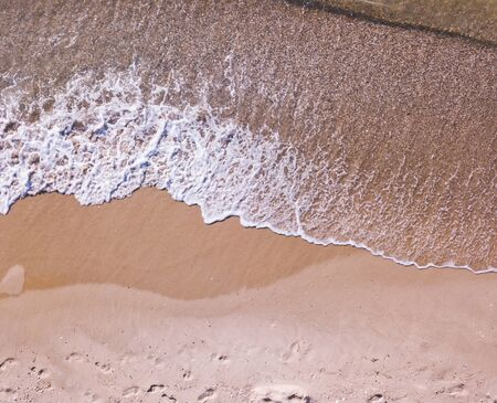 Aerial view of sandy beach and sea with waves