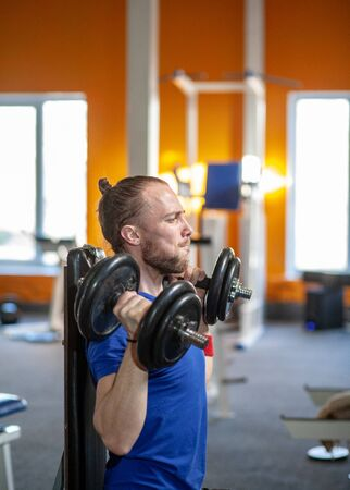 Strong man lifting weight in sport club. Closeup guy training muscles with dumbbells in gym. Handsome fitness trainer doing power lifting exercises in fitness center.