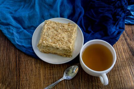 Cup of tea with cake on brown table background
