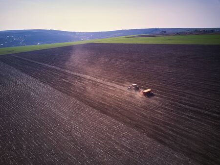 Tractor in a field performing spring sowing., top view from drone pov
