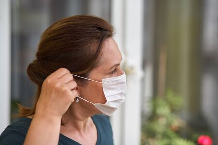 Women puts on respiratory mask. Doctor woman puts on face mask and looks at camera. Cold, flu, virus, tonsillitis, acute respiratory disease, quarantine, epidemic concept. Close-up