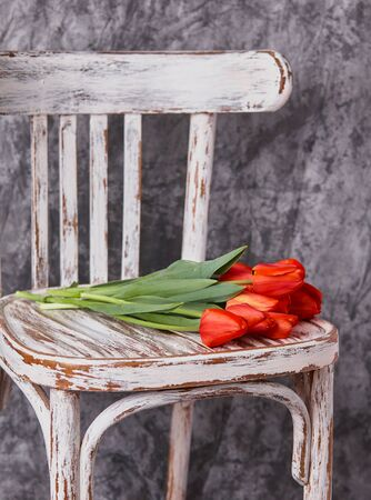 red tulips on a wooden vintage old white chair