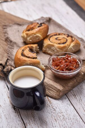 Variety of homemade puff pastry buns cinnamon served with milk cup, jam, butter as breakfast over white plank wooden background. Flat lay, space