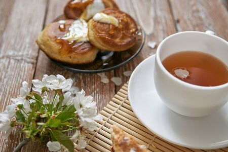 Pile of small homemade pancakes with honey, tea cup and honeycomb on wooden table