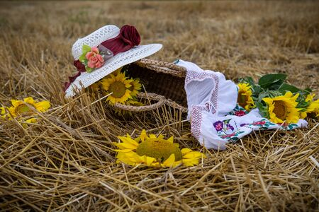 Still life of hats and baskets with sunflowers on a mowed field Standard-Bild